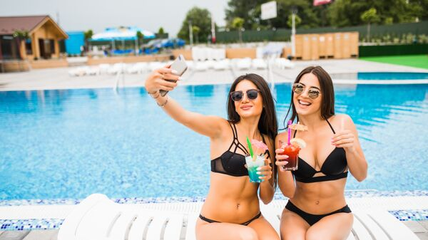 Девушки делают селфи у бассейна