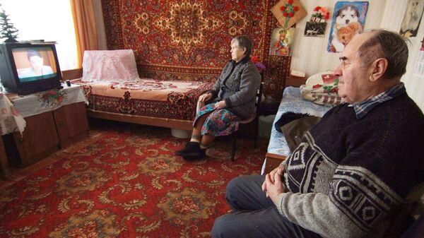 Пожилая пара смотрит телевизор
