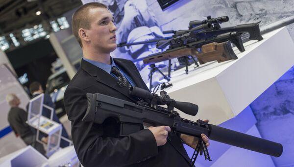 Сотрудник со снайперской крупнокалиберной бесшумной винтовкой Выхлоп на стенде компании Ростех. Архивное фото
