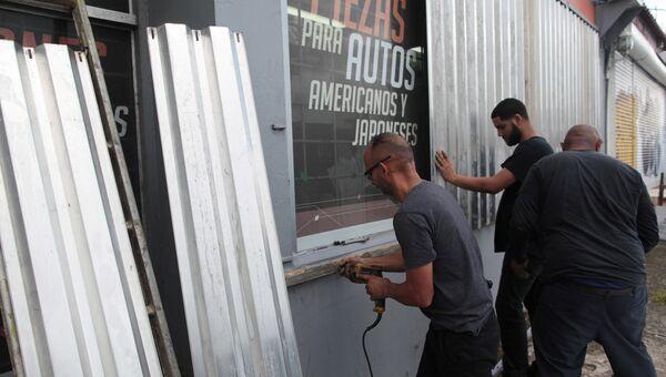Мужчины зеделывают окна автомагазина на острове Пуэрто-Рико в ожидании урагана Ирма. 5 сентября 2017