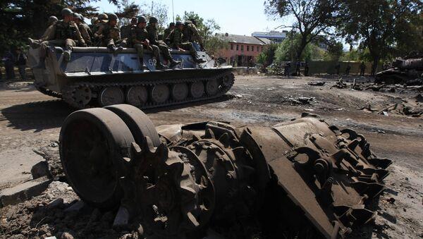 Российские военнослужащие проезжают мимо разбитой боевой техники в городе Цхинвали, подвергшемся нападению грузинских войск