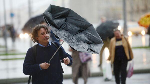 Прохожие идут на Смоленской площади во время дождя в Москве. 15 сентября 2017