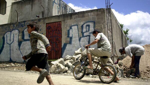 Дети играют напротив дома, разрисованного граффити о группировке Mara Salvatrucha в Гондурасе