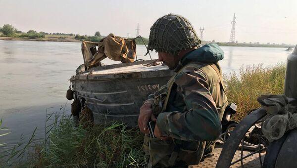 Боец сирийской армии во время подготовки к форсированию реки Ефрат в районе города Дейр-эз-Зор. 18 сентября 2017