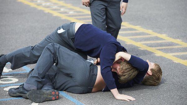 Мальчики дерутся на школьной площадке
