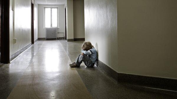 Расстроенный ребенок в пустом школьном коридоре