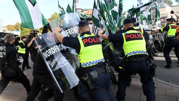 Полицейские останавливают демонстрантов Северного движения сопротивления в центре Гетеборга, Швеция. 30 сентября 2017