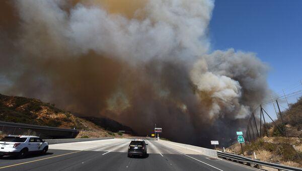 Полицейский автомобиль блокирует автостраду во время пожара недалеко от Оринджа, Калифорния, США. 9 октября 2017