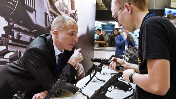 Мужчина осматривает пистолет на выставке Оружие и безопасность в Киеве
