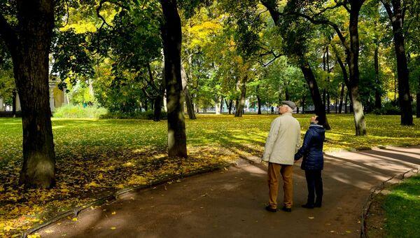 Пожилая пара гуляет в саду. Архивное фото