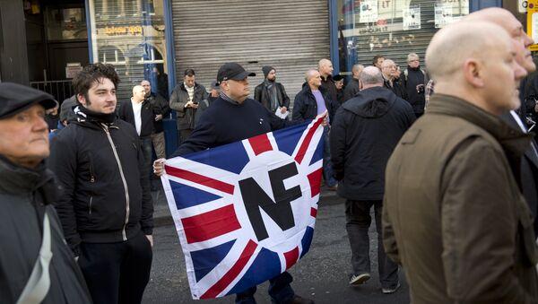 Активист с флагом правой организации Национальный фронт на демонстрации в Англии