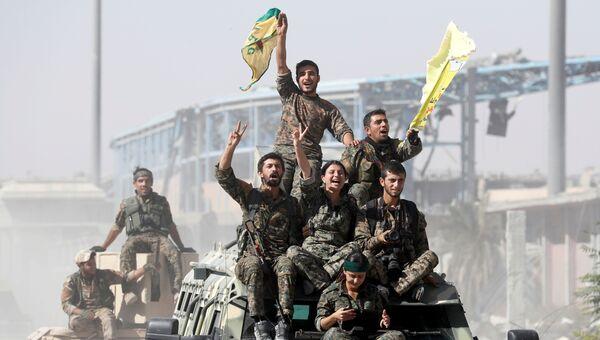 Военнослужащие Сирийских демократических сил празднуют победу в Ракке, Сирия. 17 октября 2017