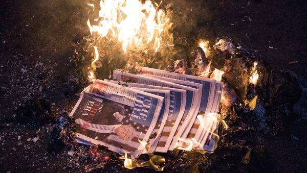Горящие газеты с изображением президента США Дональдом Трампом на главной странице, Вашингтон
