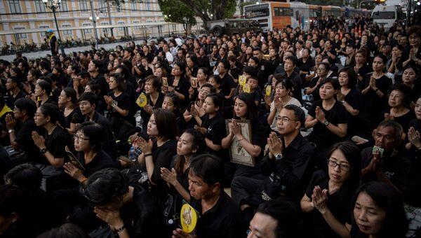 Скорбящие молятся за покойного тайского короля Пхумипона Адульядета во время шествия, передающего реликвии и его прах из Большого дворца в местный храм в Бангкоке. 29 октября 2017