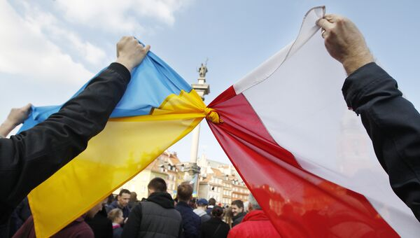 Люди держат связанные флаги Польши и Украины в Варшаве. Архивное фото
