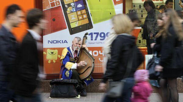 Мужчина украинском в национальном костюме играет на домре на улице Киева. 18 апреля 2013