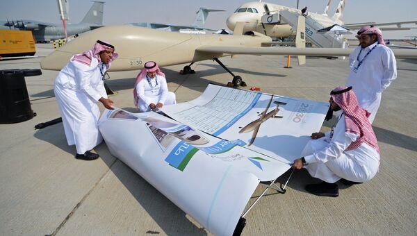 Участники монтируют баннер на Международной авиационно-космической выставке Dubai Airshow 2017