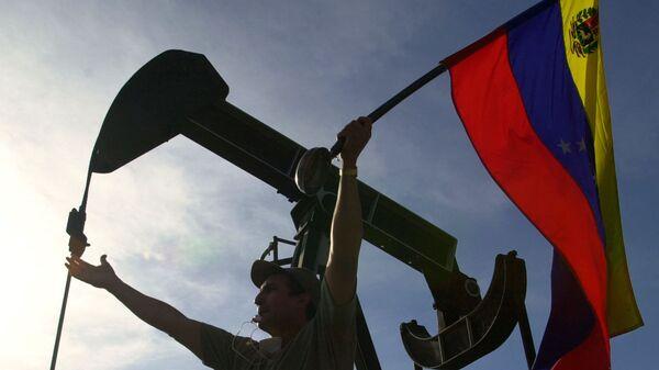 Мужчина с флагом Венесуэлы перед зданием компании PDVSA в Каракасе