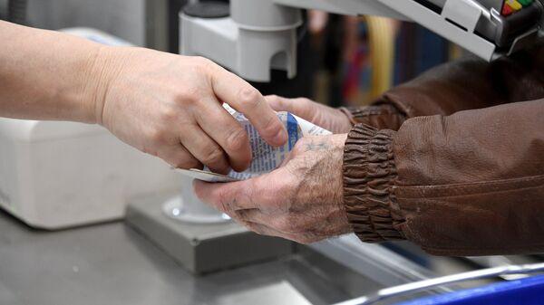 Покупательница забирает сдачу и чек в супермаркете