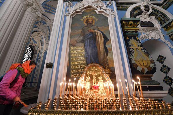Прихожанка ставит поминальную свечку в Воскресенском соборе на территории Ново-Иерусалимского мужского монастыря