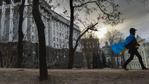 Мужчина с флагом Украины у здания правительства в Киеве, Украина