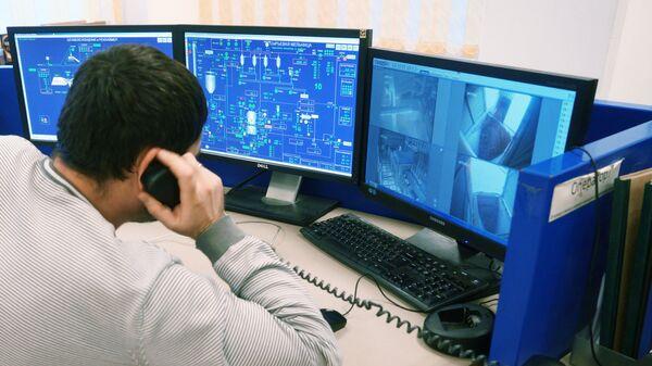 Сотрудник у пульта управления на заводе