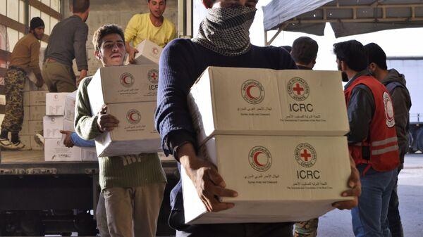 Сирийцы разгружают грузовик с гуманитарной помощью от Сирийского арабского Красного Полумесяца