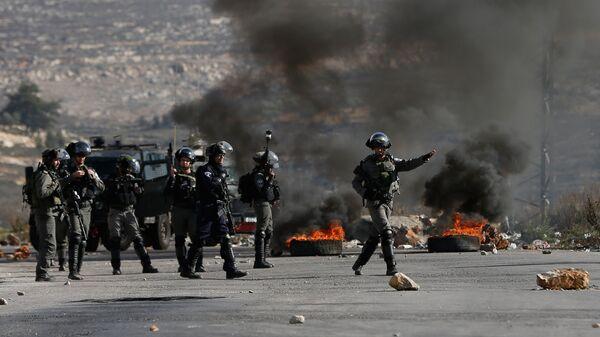 Израильские военные во время столкновений с палестинскими протестующими в районе городе Рамалла на Западном берегу. 7 декабря 2017