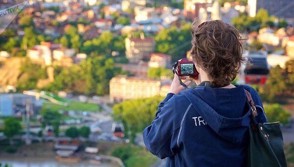 Женщина фотографирует Тбилиси