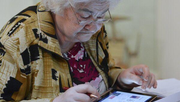 Слушательница специального проекта Обучение планшетной грамоте, организованного МВО Манеж, осваивает работу с планшетным компьютером в музее-мастерской Дмитрия Налбандяна в Москве. Архивное фото