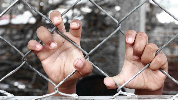 Руки ребенка, сжимающие забор