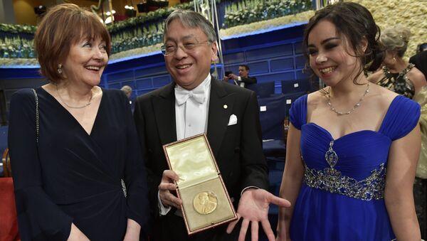 Британский автор и лауреат Нобелевской премии по литературе 2017 года Кадзуо Ишигуро позирует своей премией в окружении жены Лорны Мак Дугалл и дочери Наоми Ишигуро после церемонии вручения Нобелевской премии в Стокгольмскоме. 10 декабря 2017
