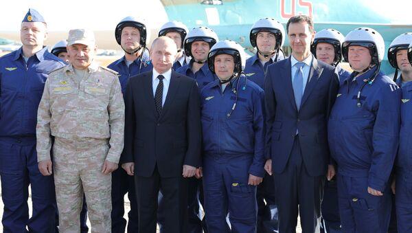 Владимир Путин, президент Сирийской Арабской Республики Башар Асад и министр обороны России Сергей Шойгу с российскими военнослужащими во время посещения авиабазы Хмеймим в Сирии. 11 декабря 2017