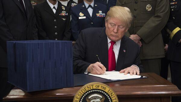 Президент США Дональд Трамп подписывает оборонный бюджет страны на 2018-й финансовый год в Белом доме, Вашингтон. 12 декабря 2017