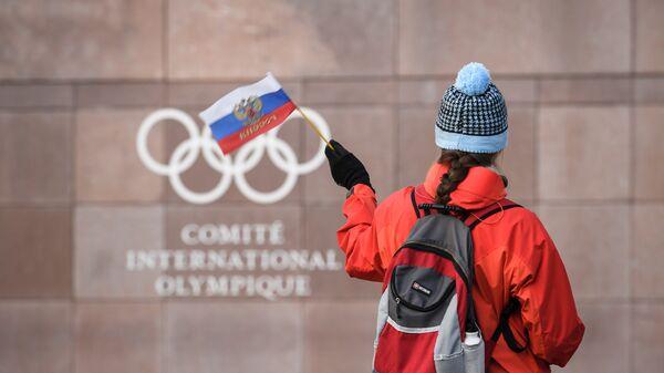 Девушка с российским флагом у штаб-квартиры МОК