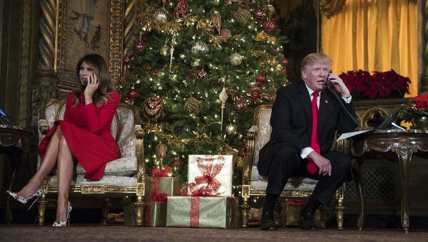 Президент США Дональд Трамп и первая леди Мелания Трамп говорят поздравляют детей по телефону во время рождественской акции в поместье президента Мар-а-Лаго в Палм-Бич, штат Флорида. 24 декабря 2017