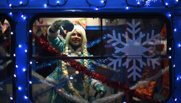 Снегурочка в салоне новогоднего трамвая, украшенный яркими светодиодными огнями, в Москве