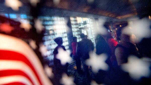 Силуэты людей на фоне американского флага. Архивное фото