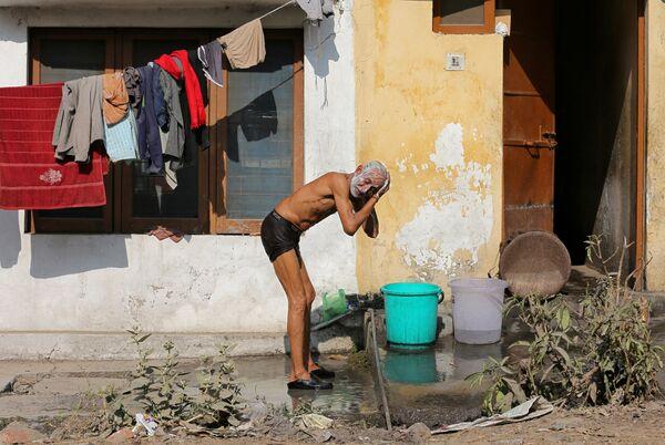 Мужчина моется на базаре в Джамму, Индия