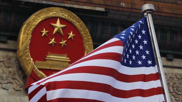 Флаг США на фоне эмблемы Китая в Пекине