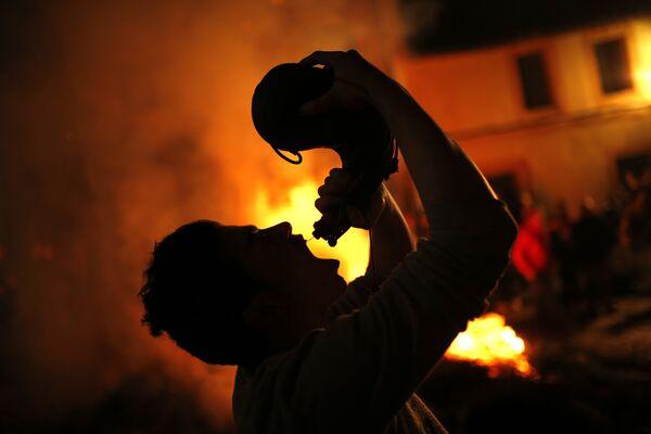 Человек пьет вино во время ритуала в честь святого Антония Аббата в Сан-Бартоломе-де-Пинарес, Испания
