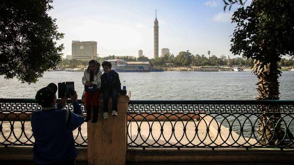Дети фотографируются на набережной в Каире. На дальнем плане: Каирская телебашня
