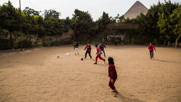 Дети играют в футбол на улиц Каира. На дальнем плане: древнеегипетская пирамида в Эль-Гизе, пригороде Каира