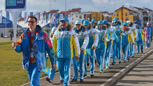 Волонтер сопровождает казахскую делегацию в прибрежной Олимпийской деревне в Сочи