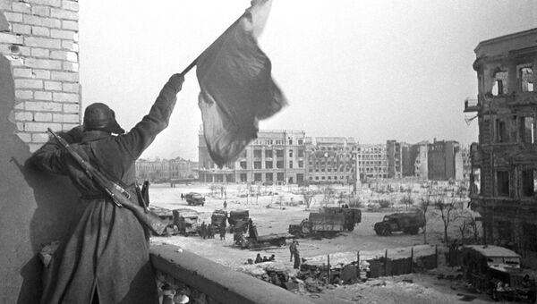 Красный флаг над площадью Павших борцов, освобожденного Сталинграда. На заднем плане — здание универмага, где был взят в плен штаб окруженной 6-й армии вермахта во главе с командующим армией фельдмаршалом Паулюсом.
