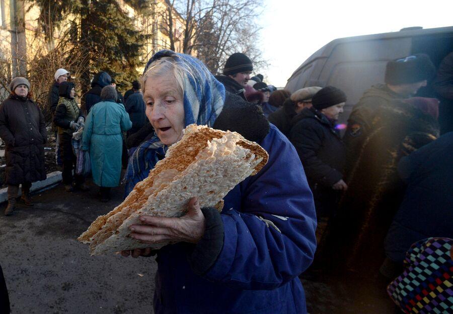 Пожилая женщина во время раздачи гуманитарной помощи жителям Дебальцево