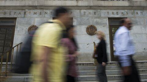 Прохожие перед зданием Министерства финансов США в Вашингтоне