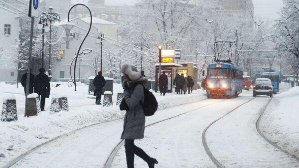 Девушка переходит трамвайные пути у остановки Метро Новокузнецкая в Москве