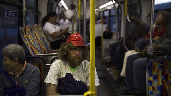 Бездомный в кепке с надписью Сделаем Америку снова великой в автобусе в Лос-Анджелесе