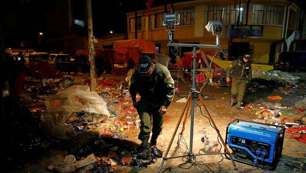 Полицейские проверяют место взрыва бутылки с газом во время парада карнавала в Оруро, Боливия. 10 февраля 2018